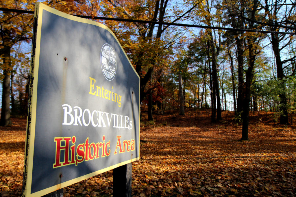"""The Brock Trail in the Fall with a sign stating, """"Entering Brockville's Historic Area."""""""