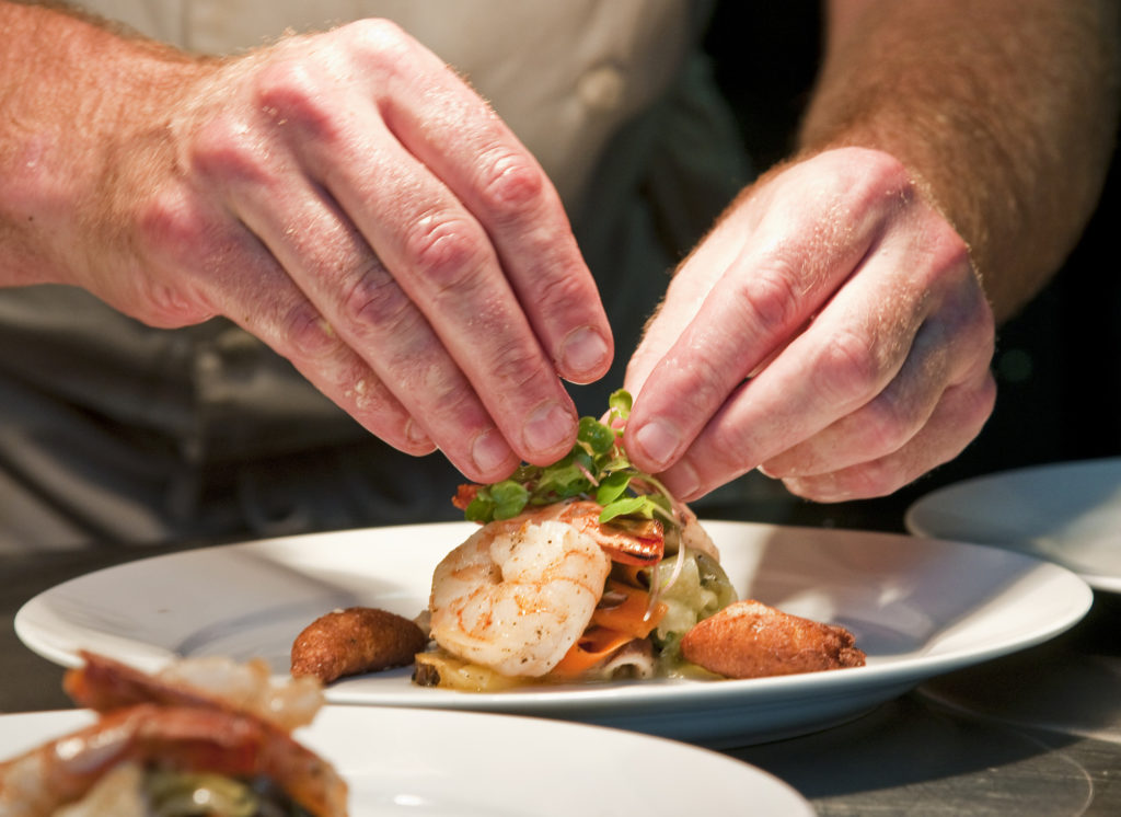 Chef's hands putting the final touches on a plate of food.