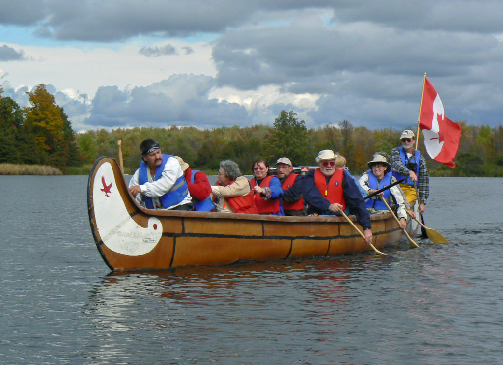 A voyageur canoe on the water with a full boat of paddlers.