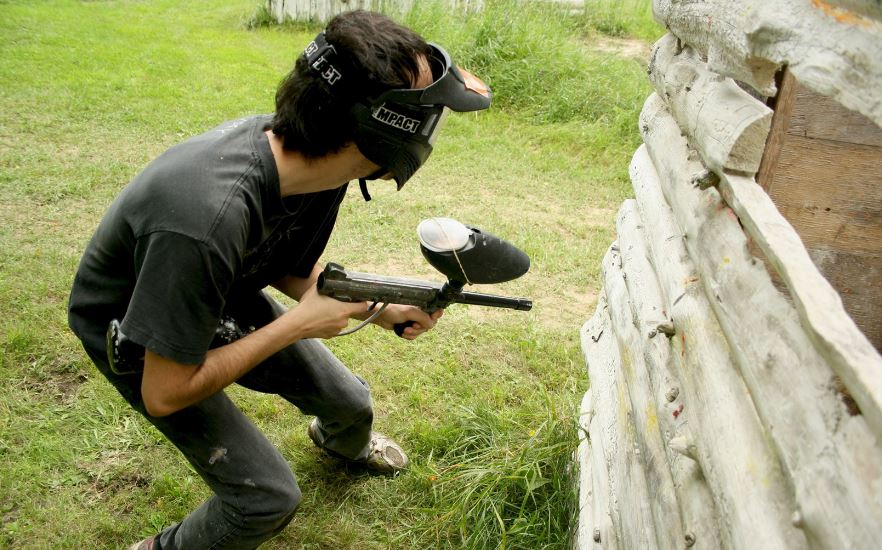 A young man with a paintball gun crouching behind the wall of a log structure.
