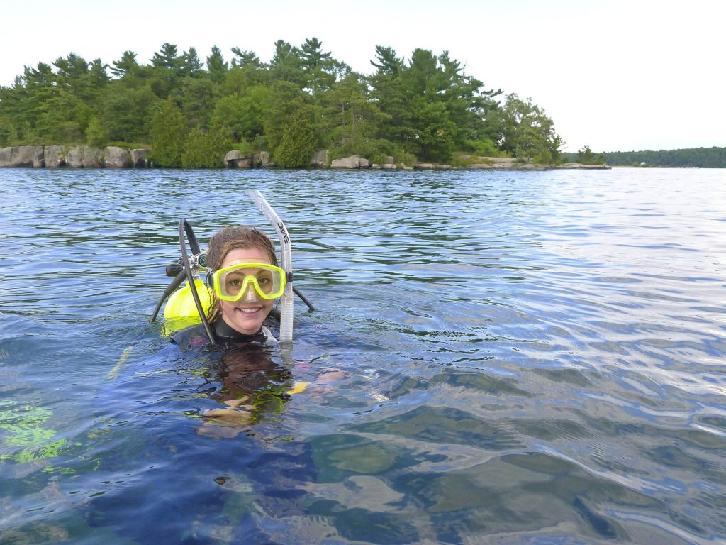 A young woman wearing scuba diving gear has her head out of the water. An island with green trees is behind her.