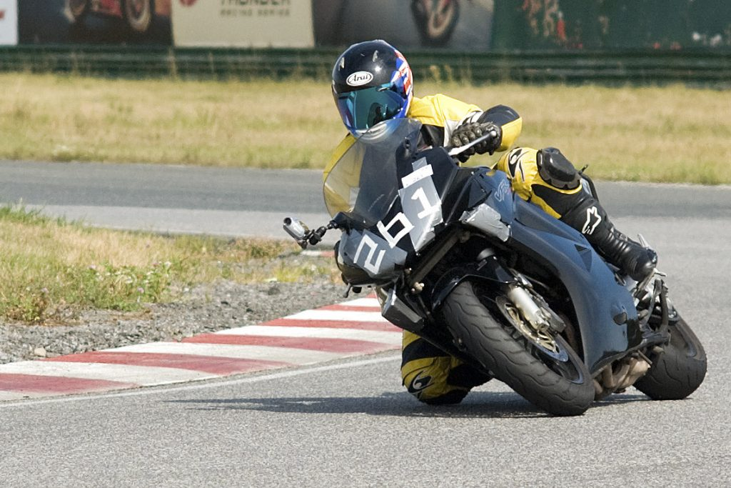 A motorcycle rider rounding a tight corner with his knee near the ground.