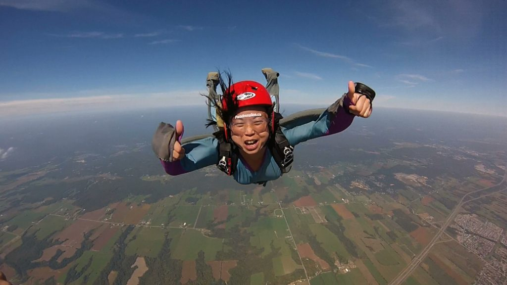 A solo skydiver with thumbs up flying high above green fields.