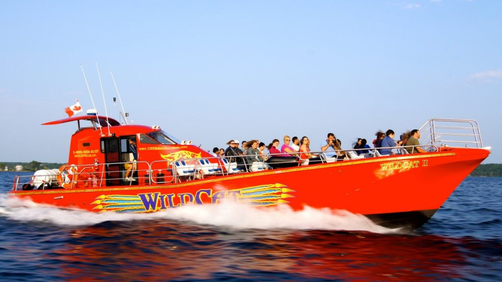 A side shot of the red WildCat boat moving swiftly through the water with a full boat of passengers.